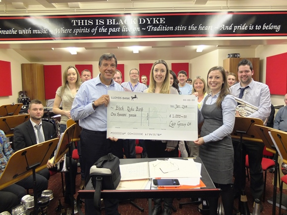 Leo Group's Melanie Rosser presents the Black Dyke Band with 1000 cheque