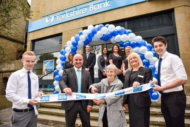 Centre - Paul Chell district manager with Customer Mrs Jean Speight cutting the ribbon and Lesley Dutton branch manager with the team at Yorkshire Bank Pudsey